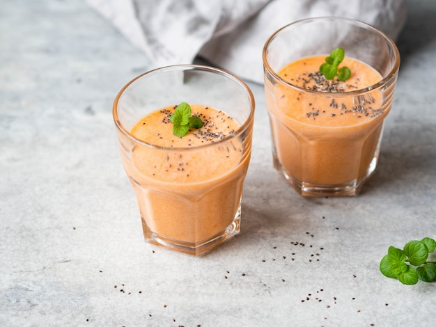 灰色の背景にチア種子と新鮮な健康的なニンジンのスムージーを2杯。コピースペース Premium写真
