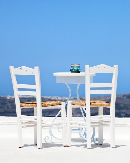 サントリーニ島の2つの白い椅子 Premium写真