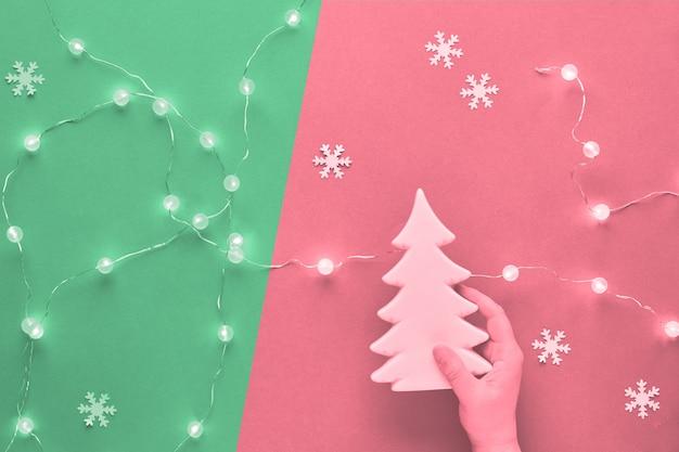 冬の休日のお祝い組成、2つのトーン、ピンクとネオミントグリーンのトーンのモノクロ画像。セラミックのモミの木の装飾を持っている手。新年やクリスマスフラットは、雪の結晶で横たわっていた。 Premium写真