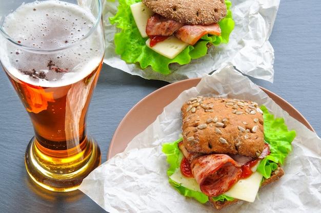 ビールのグラスとレタス、ベーコン、チーズ、紙の上のケチャップ、黒いスレートの石の2つのハンバーガーのようなサンドイッチ Premium写真