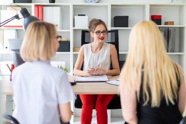 若い女の子が彼女のオフィスのテーブルに座っていて、2人の共同パートナーと話しています。 Premium写真