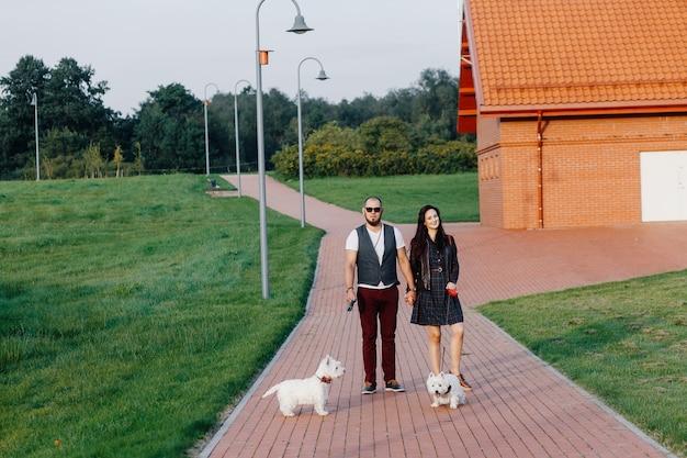 スタイリッシュなカップルが2匹の白い犬と一緒に公園を散歩します Premium写真