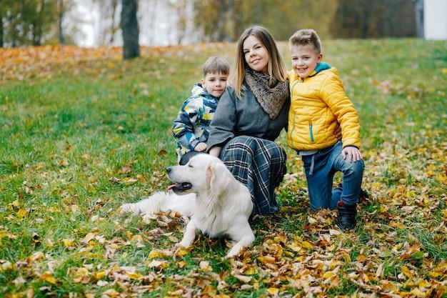 秋に公園を歩いている2人の息子と犬とママ Premium写真