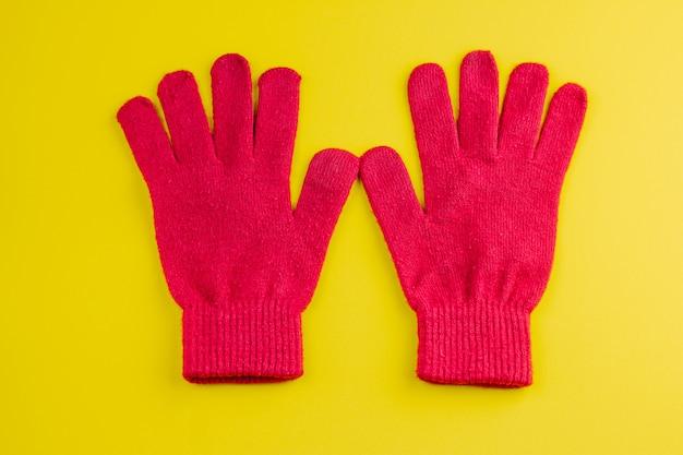 黄色に分離された2つの赤い手袋 Premium写真