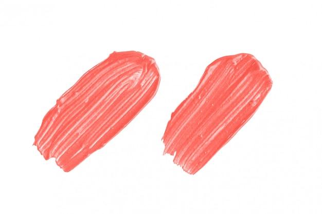 サンゴの化粧見本。トレンディな色の白い背景で隔離の2つの口紅ストロークのセット Premium写真
