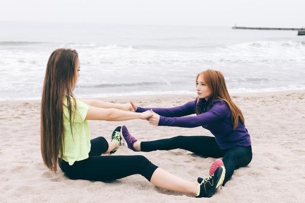 ビーチでストレッチをしているスポーツウェアの2人の女の子 Premium写真