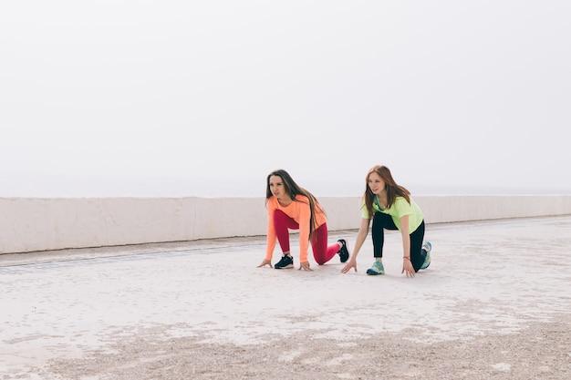 スポーツウェアの2人の細身の女の子がビーチに沿って走る準備をしています Premium写真