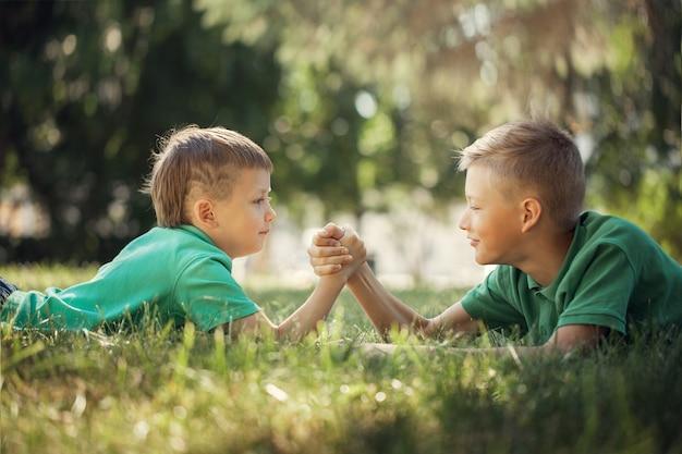 夏に緑の芝生で腕相撲に従事している2人の少年の手を握りしめ Premium写真