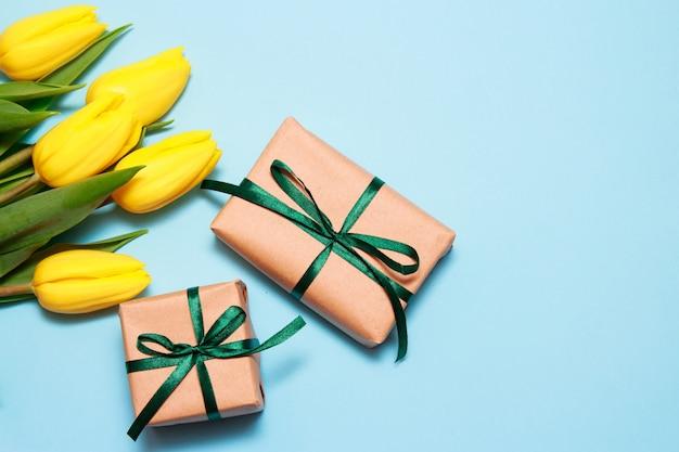 青い紙の背景に黄色のチューリップと2つのクラフトギフトの花束。 Premium写真