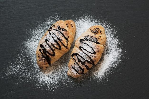 2 очень вкусных свеже испеченных круассана на предпосылке шифера. вид сверху. завтрак. Premium Фотографии