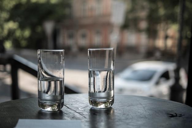 街の通りの背景にレストランのテーブルの上に水を2杯 Premium写真