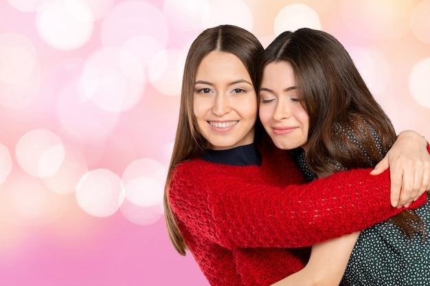 2人の美しい姉妹が抱き合って笑顔 Premium写真