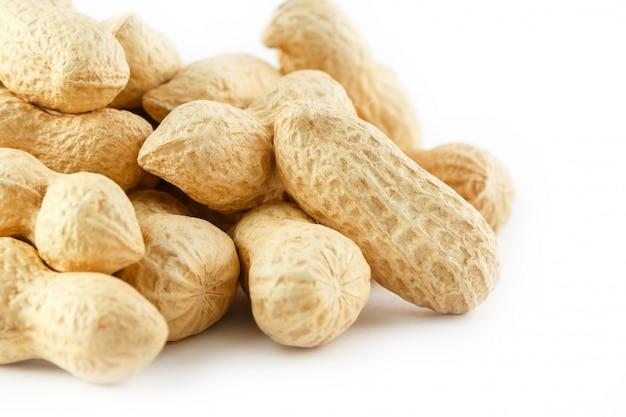 ピーナッツ。白で隔離される2つの皮をむいたナッツ。ピーナッツマクロ。 Premium写真