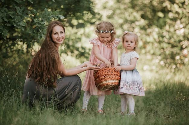 公園で娘と家族の写真ママ。春の時間、楽しんで娘と美しい女性の屋外で2人のかわいい子供を持つ若い母親の写真 Premium写真