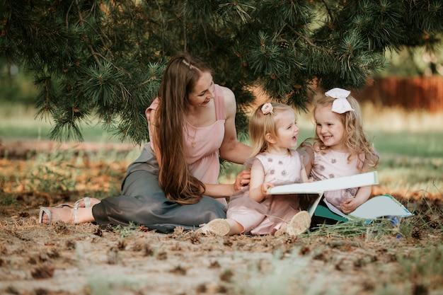 Внешний портрет маленькой девочки 2 читает книгу на траве с матерью. у нее приятное выражение лица, и она выглядела очень расслабленной в руках своей матери. Premium Фотографии