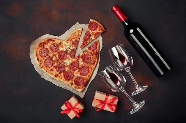 モッツァレラチーズ、ソーセージ、ワインボトル、2つのワイングラスを添えたハート型のピザ。さびた背景にバレンタインの日グリーティングカード。 Premium写真