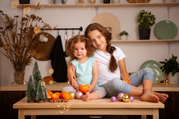 クリスマスキッチンでみかんを食べる2人の女の子 Premium写真