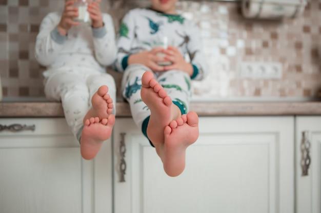 2人の赤ちゃん男の子はパジャマで台所で朝食を楽しんでいます Premium写真