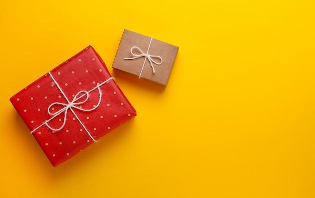 黄色の背景にクラフト紙に包まれた2つの贈り物。 Premium写真