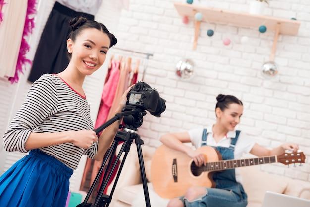 スカート付きシャツの2人のファッションブロガーの女の子がギターを弾く Premium写真