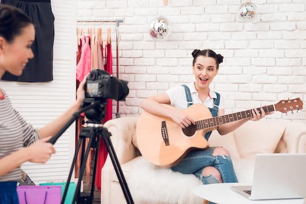 2人のファッションブロガーの女の子がカメラでギターを弾きます。 Premium写真