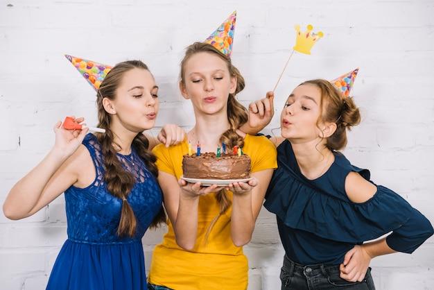 誕生日ケーキのろうそくを吹いている3人の10代女性の友人 無料写真