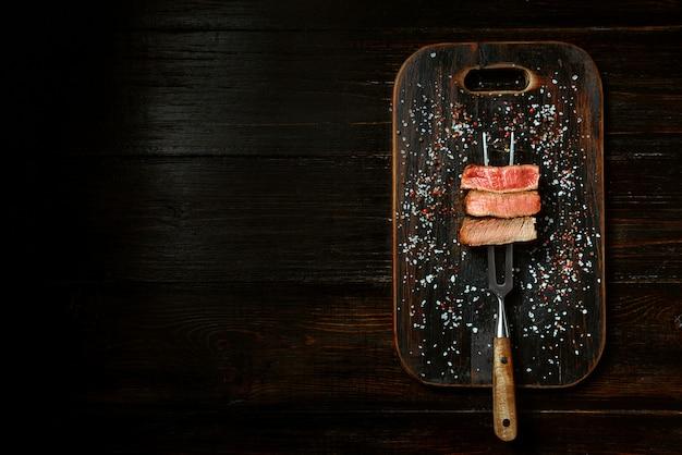 肉用のフォークに3枚の肉。 3種類の肉のロースト、レア、ミディアム、よくできています。 Premium写真