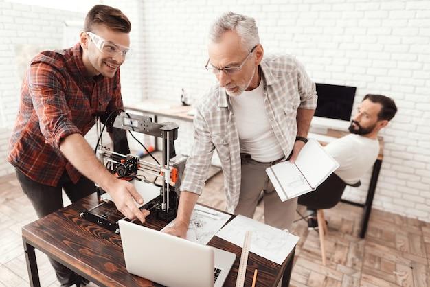 3人の男性がフォームを印刷するために自作の3dプリンタをセットアップしました Premium写真