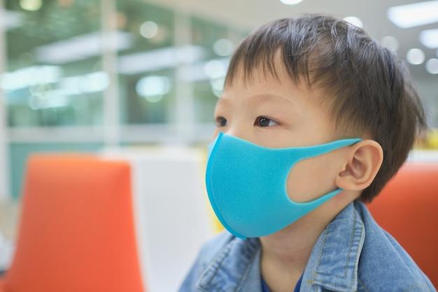 Милый маленький азиатский малыш 3-4 лет, носящий защитную медицинскую маску против загрязнения воздуха pm 2.5, малыш сидит на диване и ждет врача Premium Фотографии