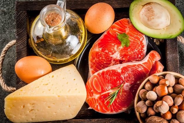 Здоровые натуральные продукты продукты со здоровыми жирами омега-3 омега-6 ингредиенты и продукты: форель (лосось), оливковое масло, орехи, авокадо, сыр, яйца, на темном каменном столе. Premium Фотографии