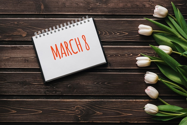 木製の茶色のテーブルボード上の白い花チューリップ。 3月8日のレタリングとグリーティングカード Premium写真