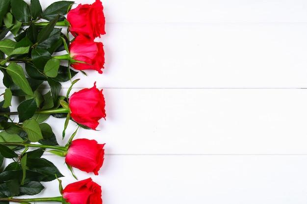 白い木製のテーブルにピンクのバラ。母の日3月8日のコピースペーステンプレート Premium写真