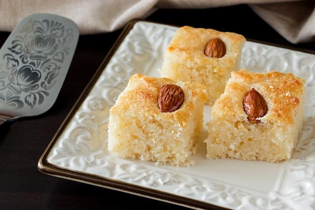 クローズアップ3個入りbasbousa伝統的なアラビア語のセモリナケーキとアーモンドナッツオレンジの花の水。スペースをコピーします。暗い背景 Premium写真