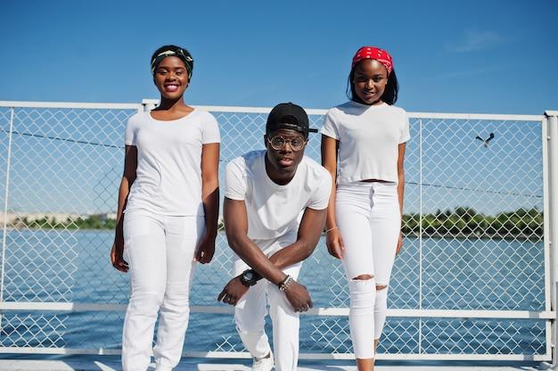3人のスタイリッシュなアフリカ系アメリカ人の友人、cageとビーチの桟橋で白い服を着ます。若い黒人のストリートファッション。 2人のアフリカの女の子と黒人男性。 Premium写真