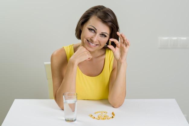 Улыбается женщина, принимая таблетки рыбьего жира омега-3. витамин d, e, a капсулы рыбьего жира Premium Фотографии