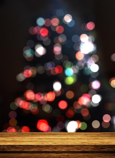 ピンぼけのクリスマスツリーを見渡す3 d木製テーブル 無料写真