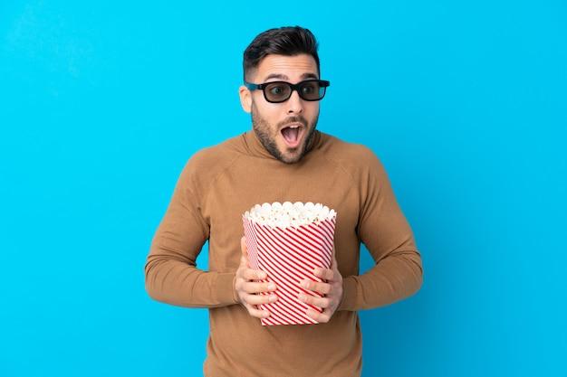 3 dメガネに驚いて、ポップコーンの大きなバケツを持って若いハンサムな男 Premium写真