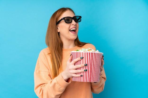 3 dメガネとポップコーンの大きなバケツを保持している若い赤毛の女性 Premium写真