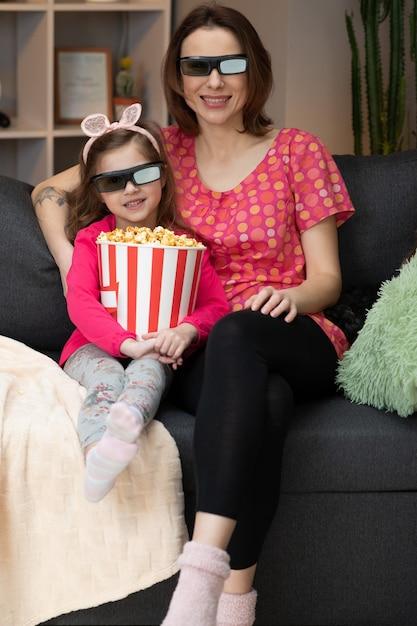 テレビを見ているとポップコーンを食べて3 dメガネを着ている女の子を持つ女性。家族の時間は、リビングルームのコンセプトのソファーに若い女の子の子供とリラックスします。 Premium写真
