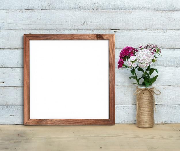 塗られた白い木製の背景に木製のテーブルの上に甘いウィリアムの花束の近くの正方形の古い木製フレームモックアップが立っています。素朴なスタイル、シンプルな美しさ。 3 dのレンダリング。 Premium写真