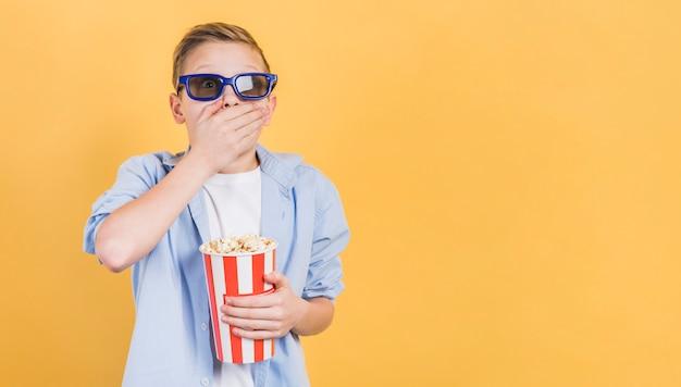 黄色の背景に手で立ってポップコーンバケツを保持している3 dメガネをかけてショックを受けた少年 無料写真