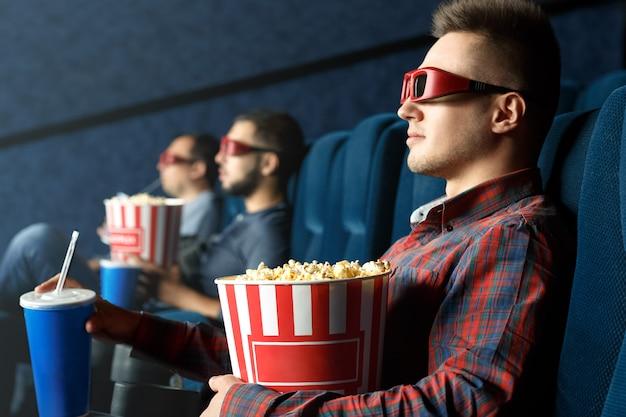 彼の寒い日。ポップコーンとドリンクで映画を見て3 dメガネをかけてリラックスしたハンサムな男性 Premium写真