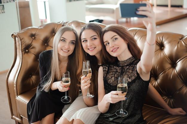3人の若い女の子がレストランでselfie写真をやっています。 Premium写真