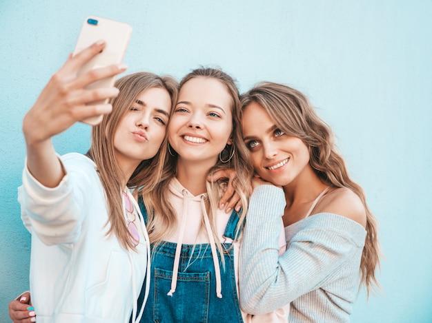 夏服の3人の若い笑顔の流行に敏感な女性。スマートフォンでselfieセルフポートレート写真を撮る女の子。壁の近くの通りでポーズをとるモデル。肯定的な顔の感情を示す女性 無料写真