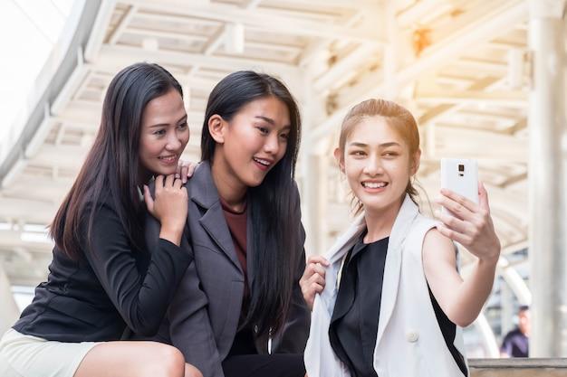 3つのかわいいアジアの女性はselfieであり、面白い女の子は自分で写真を撮ります。 Premium写真