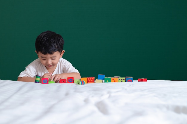 3 years old asian boy play toy or square block puzzle on green chalkboard or school board background Premium Photo
