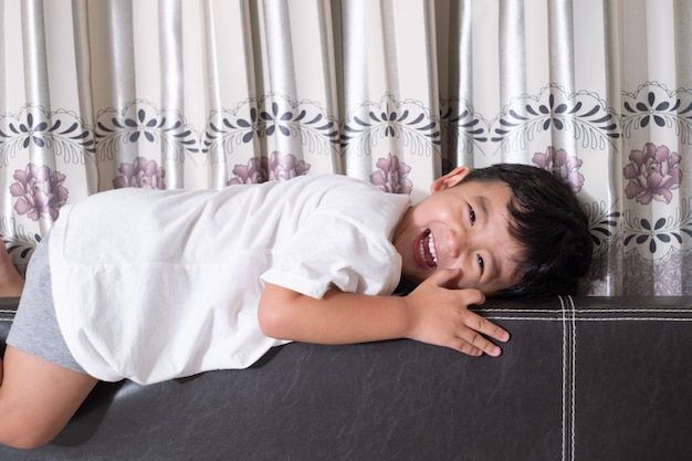 3 years old little cute asian boy at home on the bed, kid lying playing and smiling on white bed Premium Photo