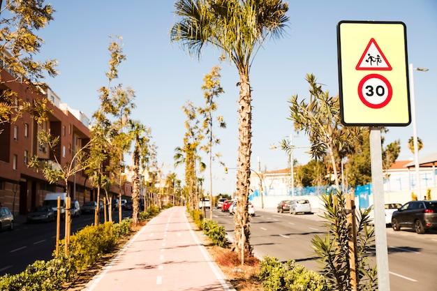 30 знак ограничения скорости на городской улице и велосипедной дорожке с зелеными деревьями Бесплатные Фотографии