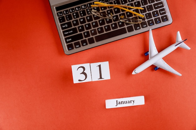 31 january calendar with accessories on business workspace office desk on computer keyboard, airplane, glasses red background Premium Photo