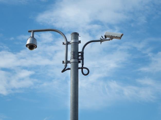 Купольная камера видеонаблюдения и камеры видеонаблюдения на 360 градусов установлены на колонне против голубого неба. Premium Фотографии